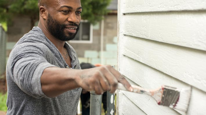 African-American man painting a house wall