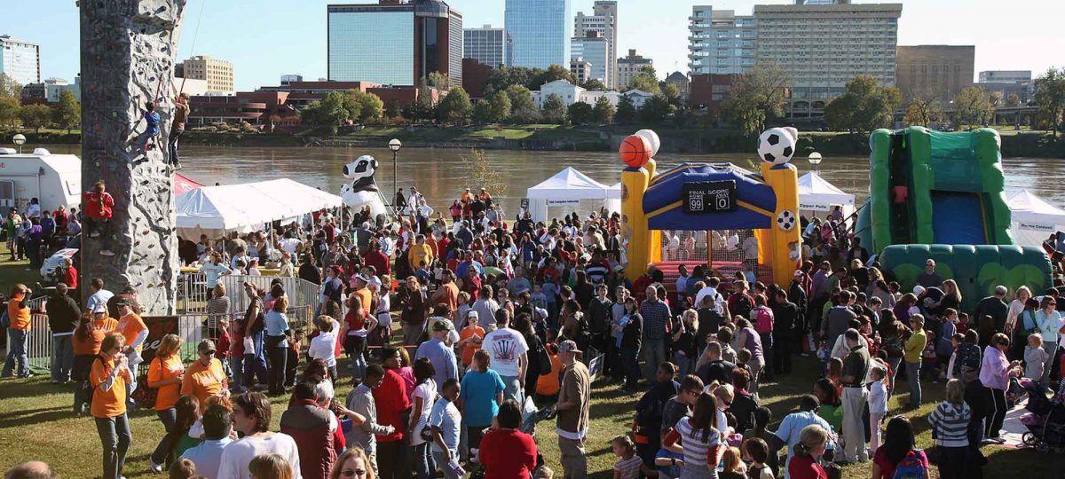 citywide event by river, with downtown Little Rock in background