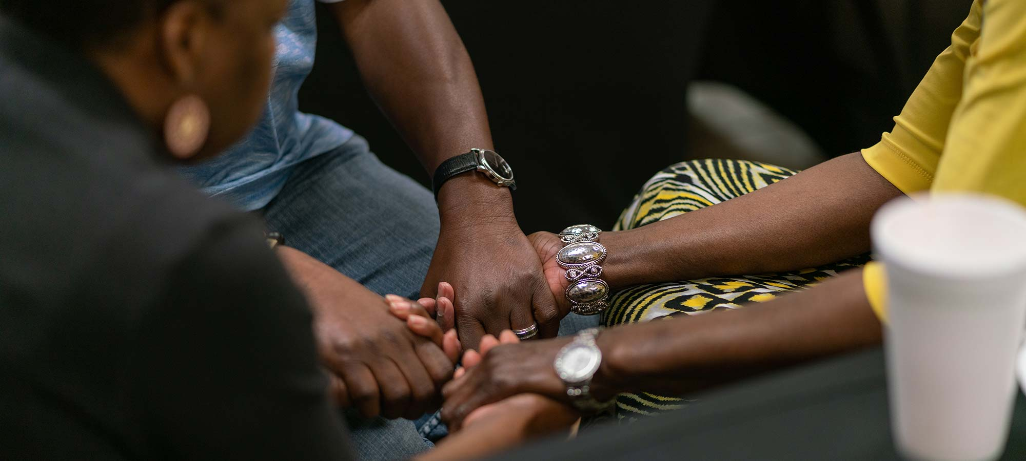 several people's hands clasped in prayer